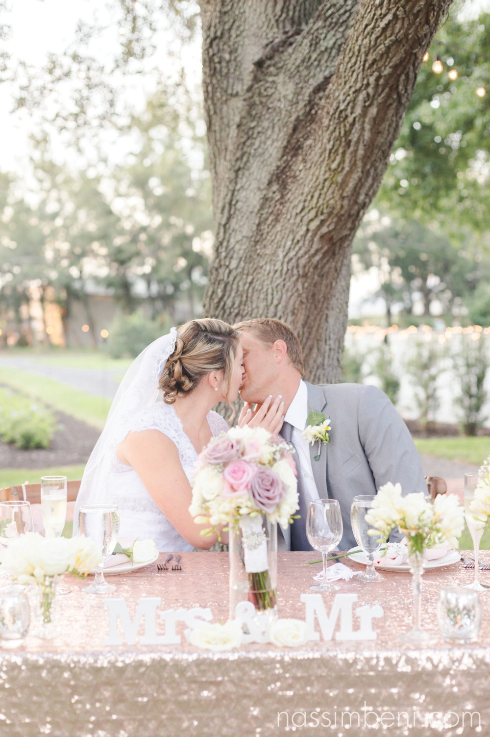 bride and groom at sweetheart table kiss by nassimbeni photography