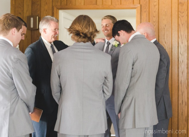 groomsmen, father of the bride and pastor pray over groom before wedding ceremony at bellwood plantation by nassimbeni photography