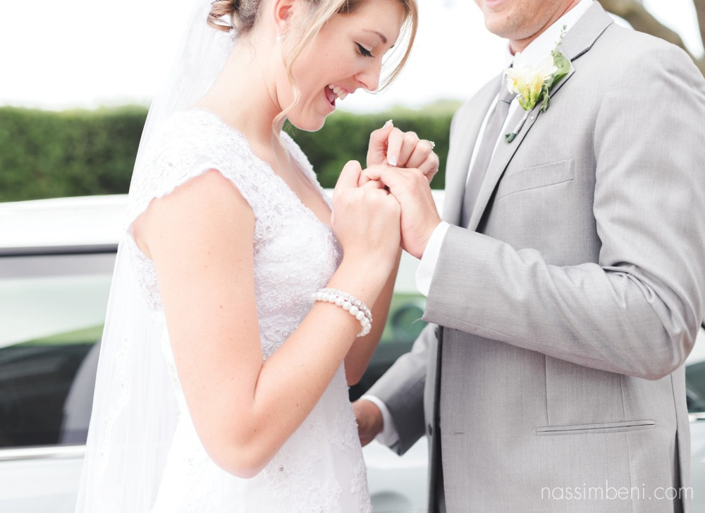 bride points out grooms wedding band in florida plantation wedding by nassimbeni photography