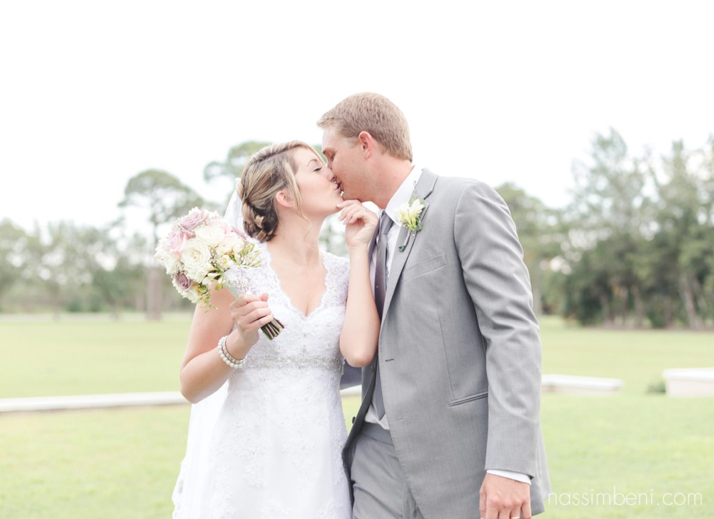 bride kisses groom walking in front of bellewoods mansion in vero beach by nassimbeni photography