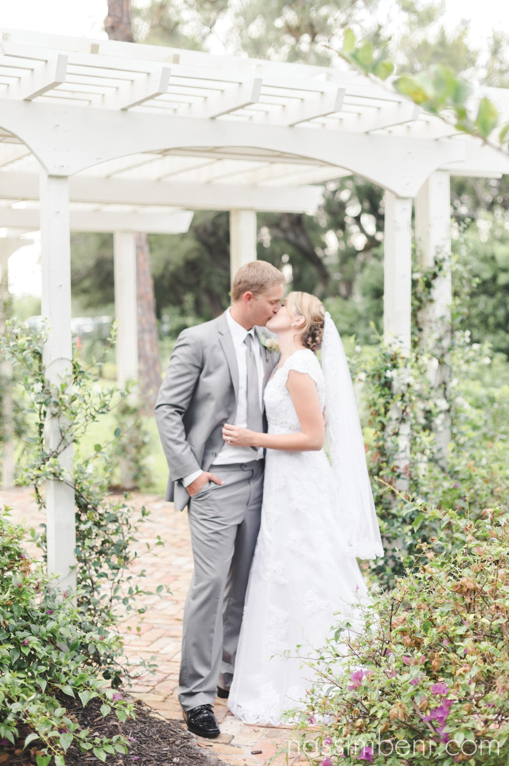 bride and groom under garden arch ceremony location for bellewood plantation wedding by nassimbeni photography