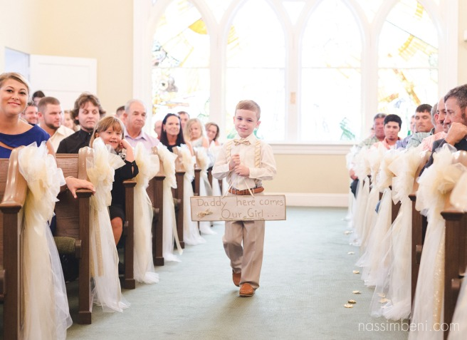 grooms son walking down aisle as best little man with daddy here comes our girl sign by nassimbeni photography