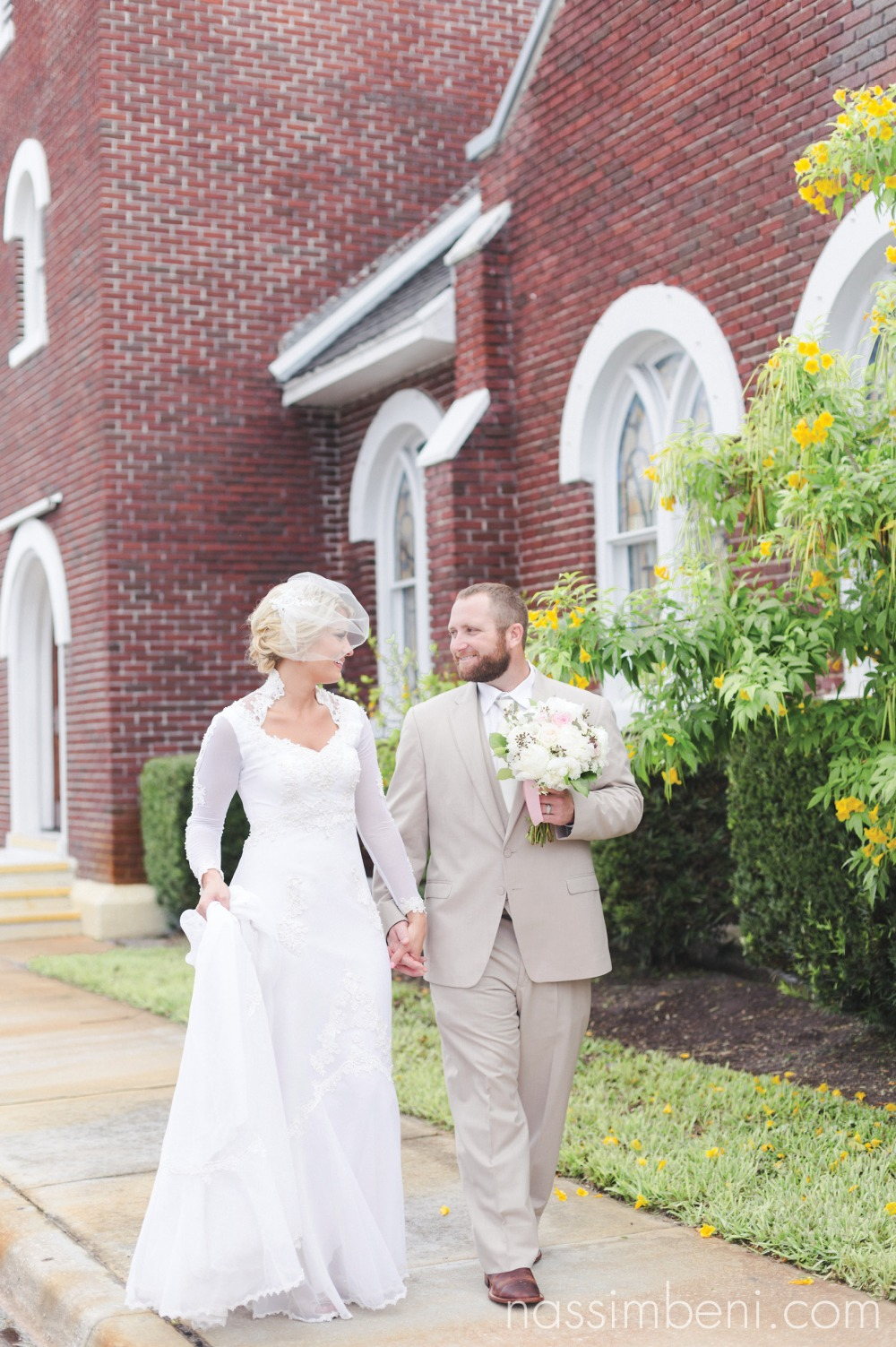 bride and groom walk in front of first united methodist church in okeechobee florida by nassimbeni photography