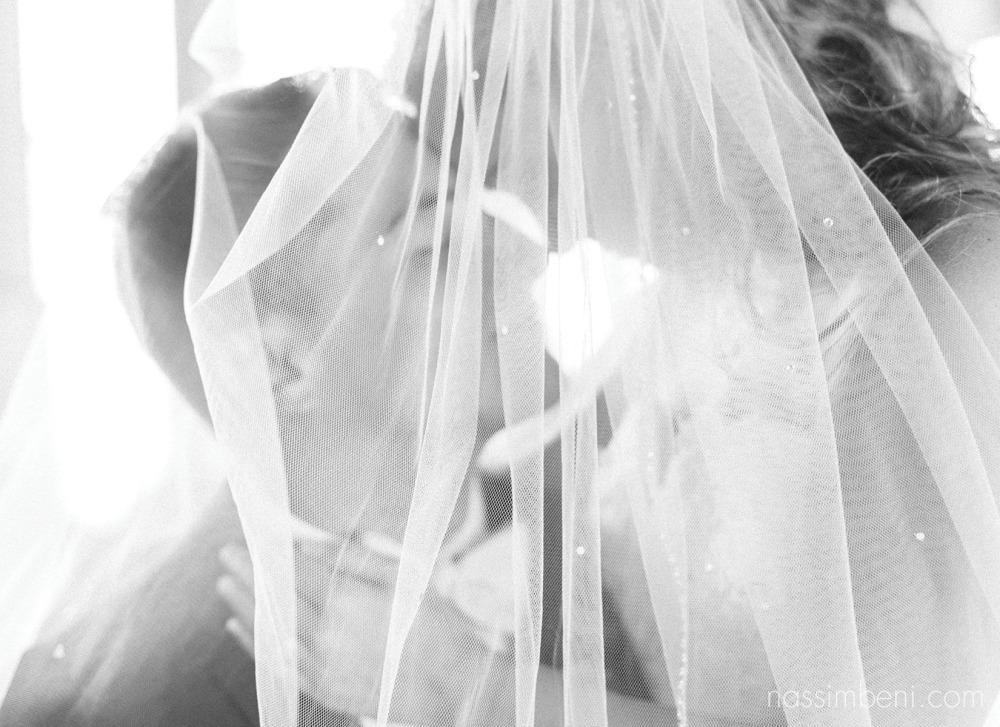 bride and groom under brides veil at crane creek promenade park