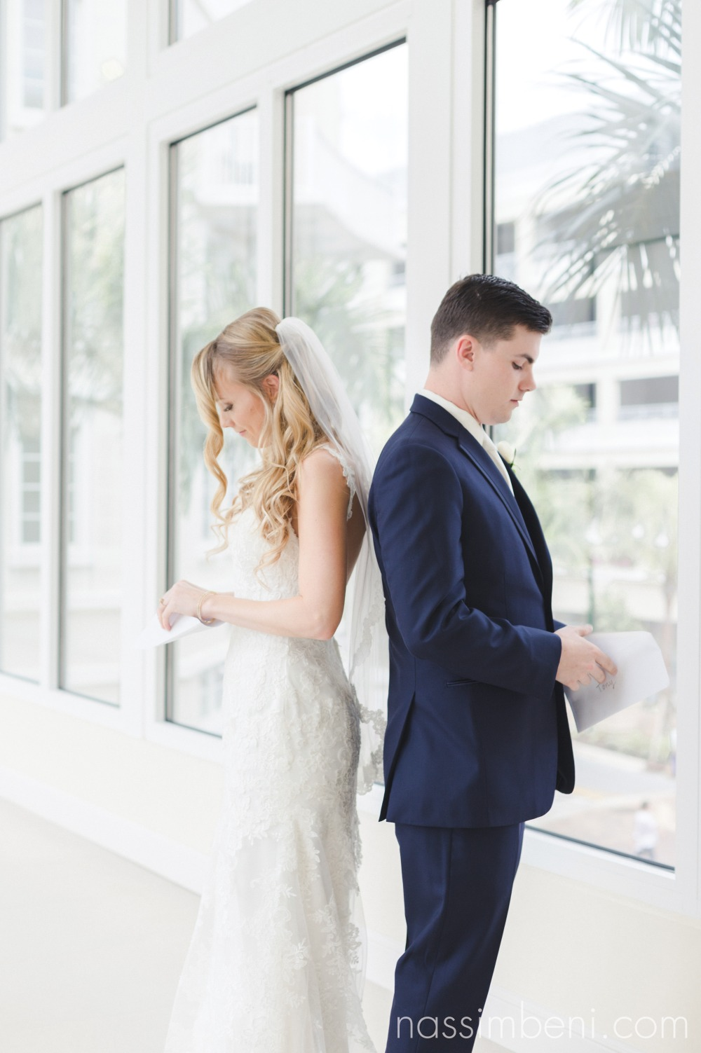 bride and groom read notes from each other before the first look at the wyndham grand at harbourside place in jupiter florida by nassimbeni photography