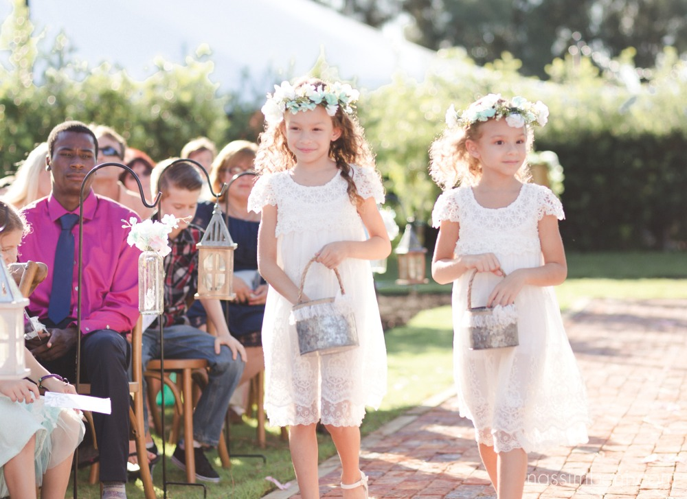 flower girls with blue flower crowns walk down aisle at bellewood plantation by Nassimbeni Photography