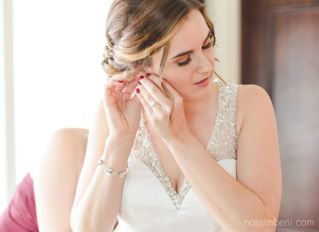 bride putting earring on at kimpton vero beach hotel and spa by vero beach wedding photographer Nassimbeni Photography