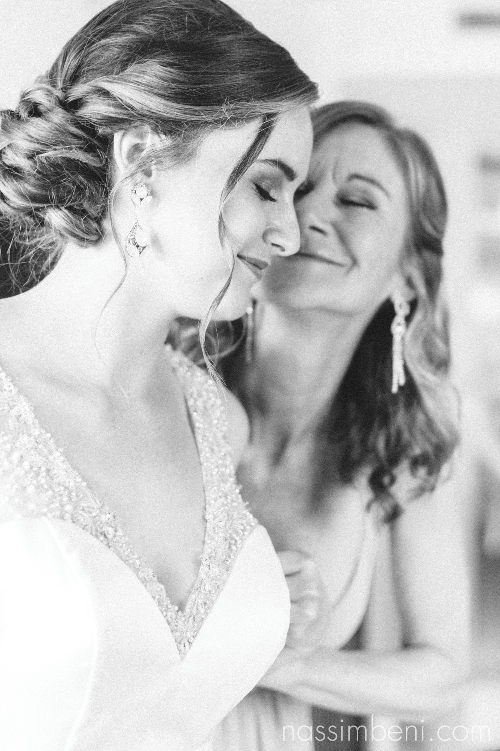 mom gives bride a kiss right after helping her put her gown on by Nassimbeni Photography