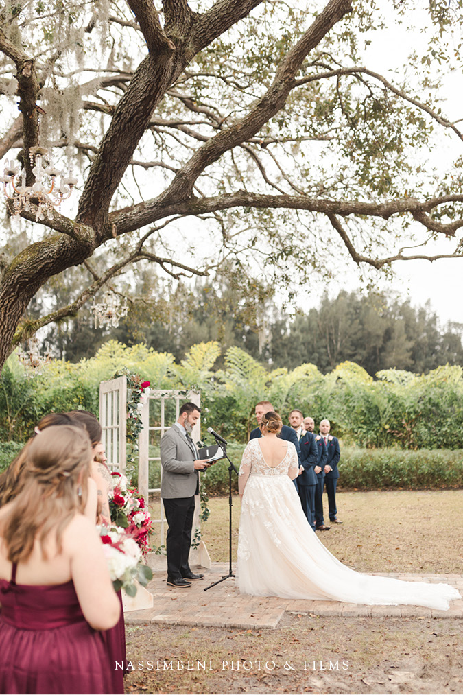 ceremony under oak tree at the lake house